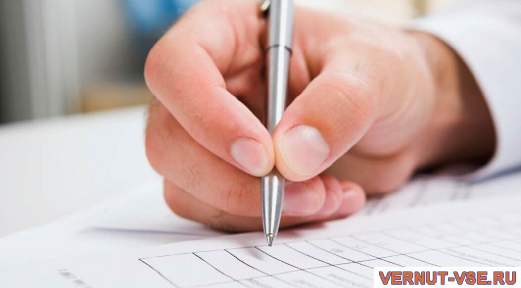 Мужская рука с ручкой над бумагой