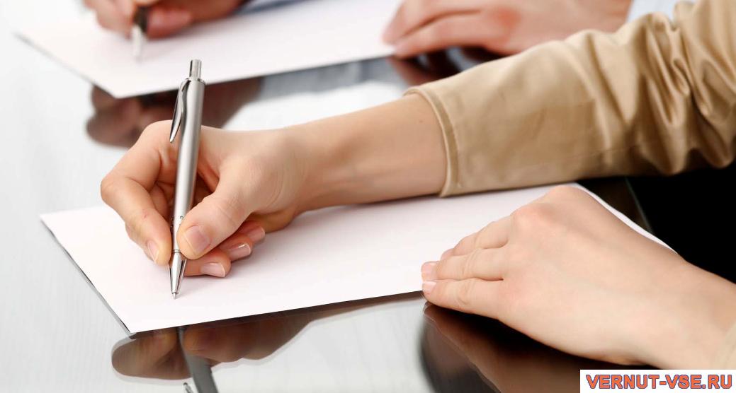 Ручка в мужской руке над листом бумаги