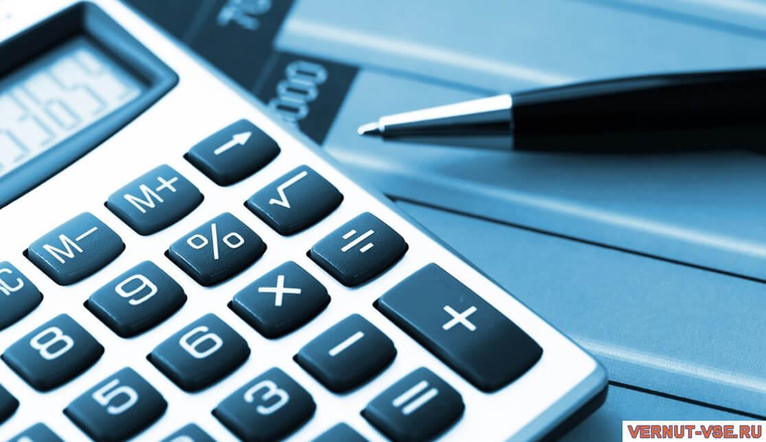 Включенный калькулятор и ручка, лежащие на столе