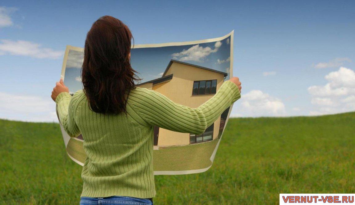Женщина, держащая план дома на фоне поля