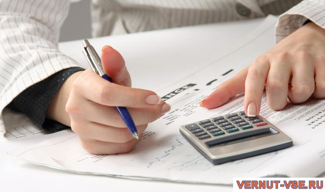 Женская рука на калькуляторе над документами