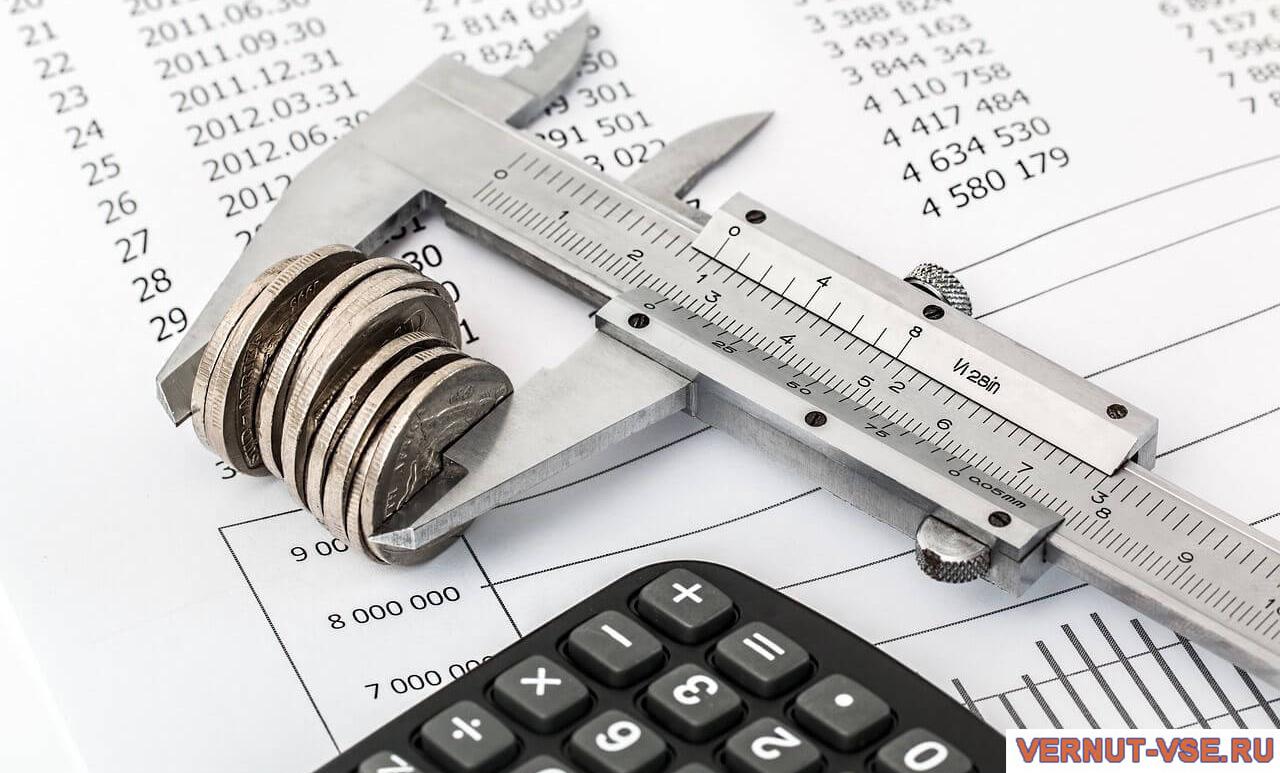 Калькулятор и штангенциркуль с монетами на документе