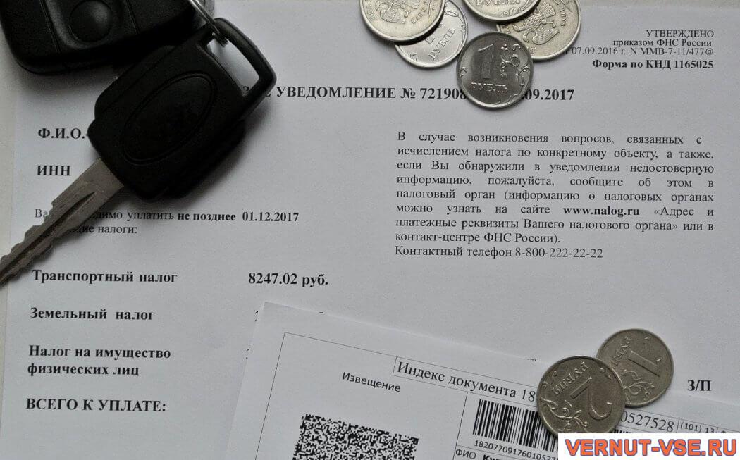 Ключ и монеты, лежащие на налоговом уведомлении