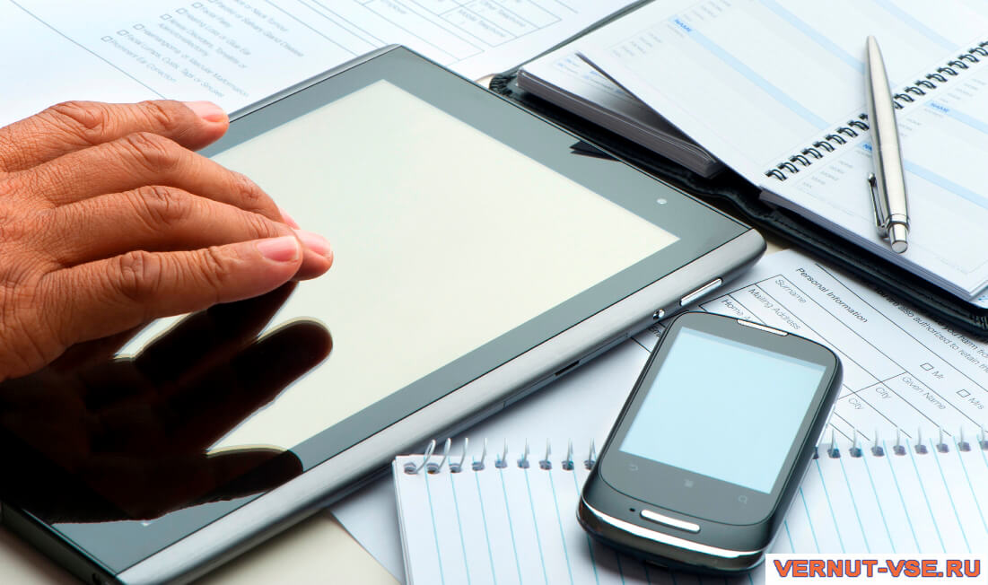 Мужская рука над планшетом рядом со смартфоном