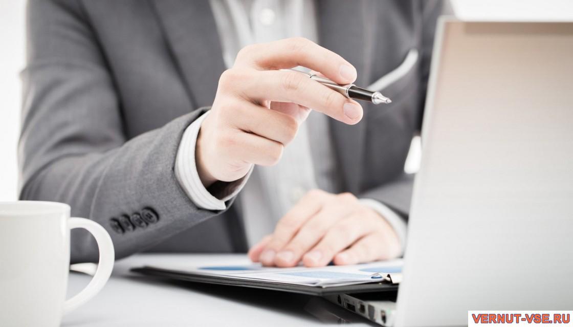 Мужская рука, показывающая ручкой на экран ноутбука