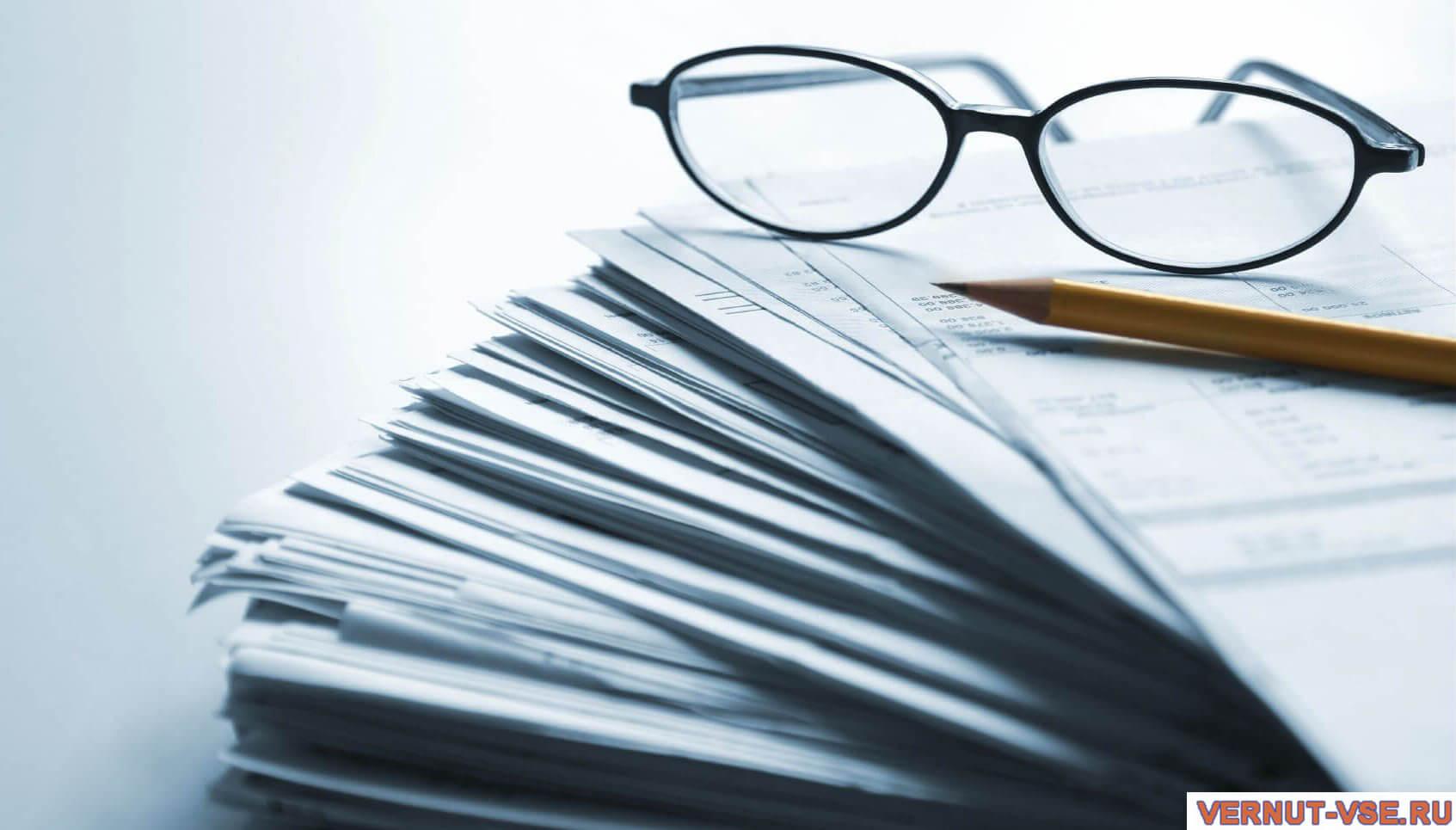 Очки и карандаш на документах