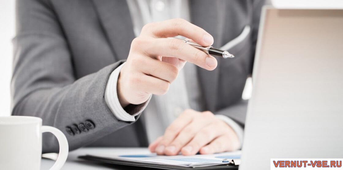 Ручка в мужской руке напротив экрана ноутбука