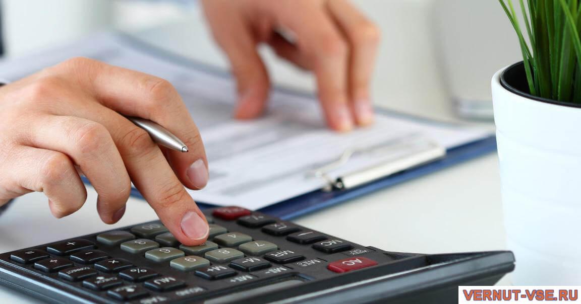 Руки на калькуляторе и документах