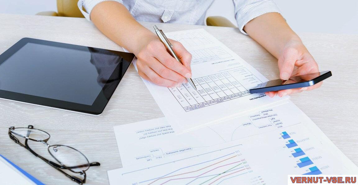 Смартфон и ручка в женских руках над документами