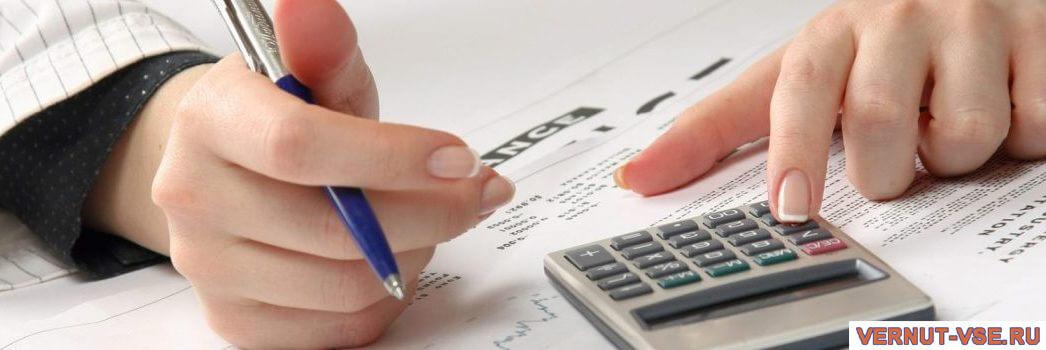 Женские руки с ручкой и калькулятором